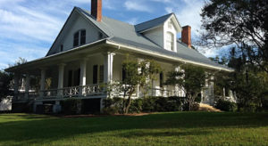 exterior view of white plantation style home with centered second floor dormer taken from green lawn