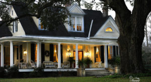 exterior of white victorian home with front porch lights on